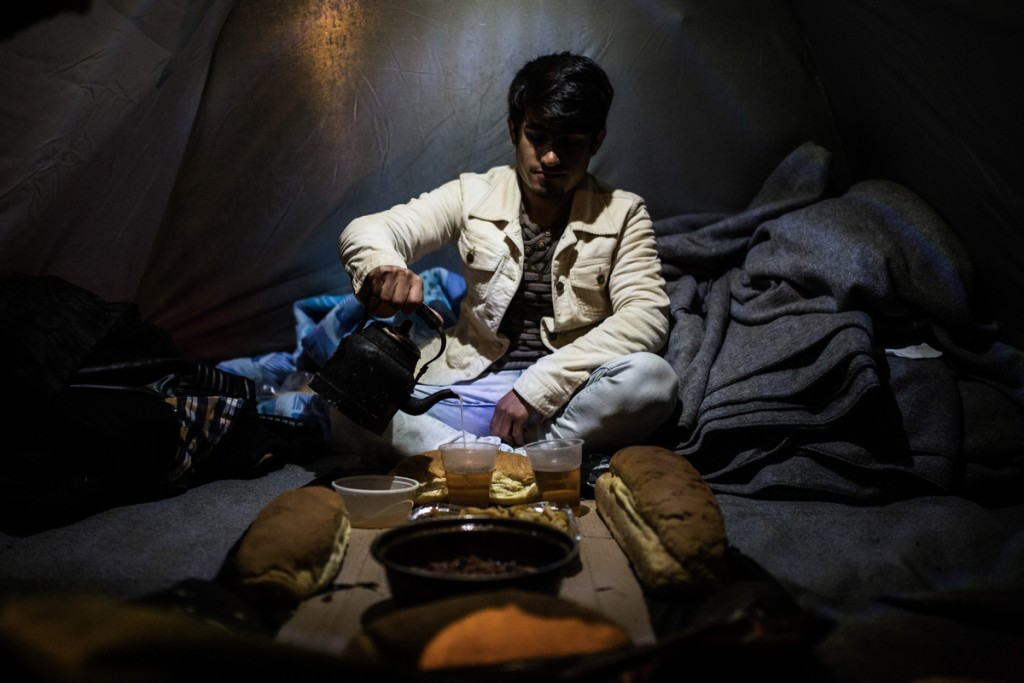 Mohammed Abdul from Afghanistan fills a plastic glass with tea as before a dinner with his friends inside a tent at the refugee camp at the Greek - FYROM border near the village of Idomeni on March 11, 2016.